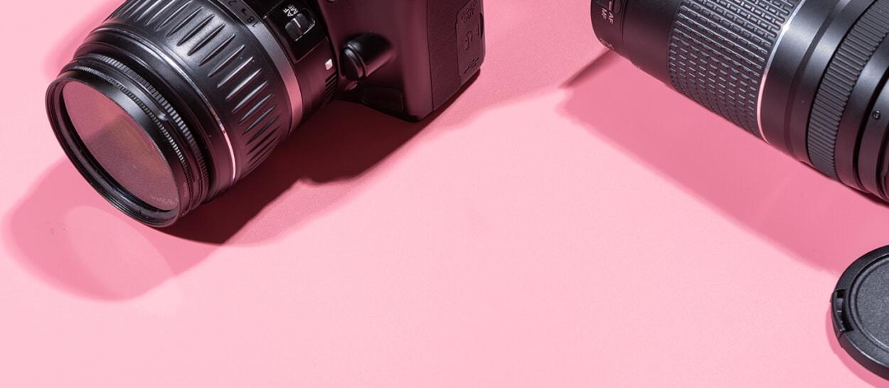 Professional camera and lens on pink backdrop for Thimble customer spotlight - Alex Gasaway