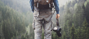 Adventurous travel photographer in forest for photographer insurance by Thimble