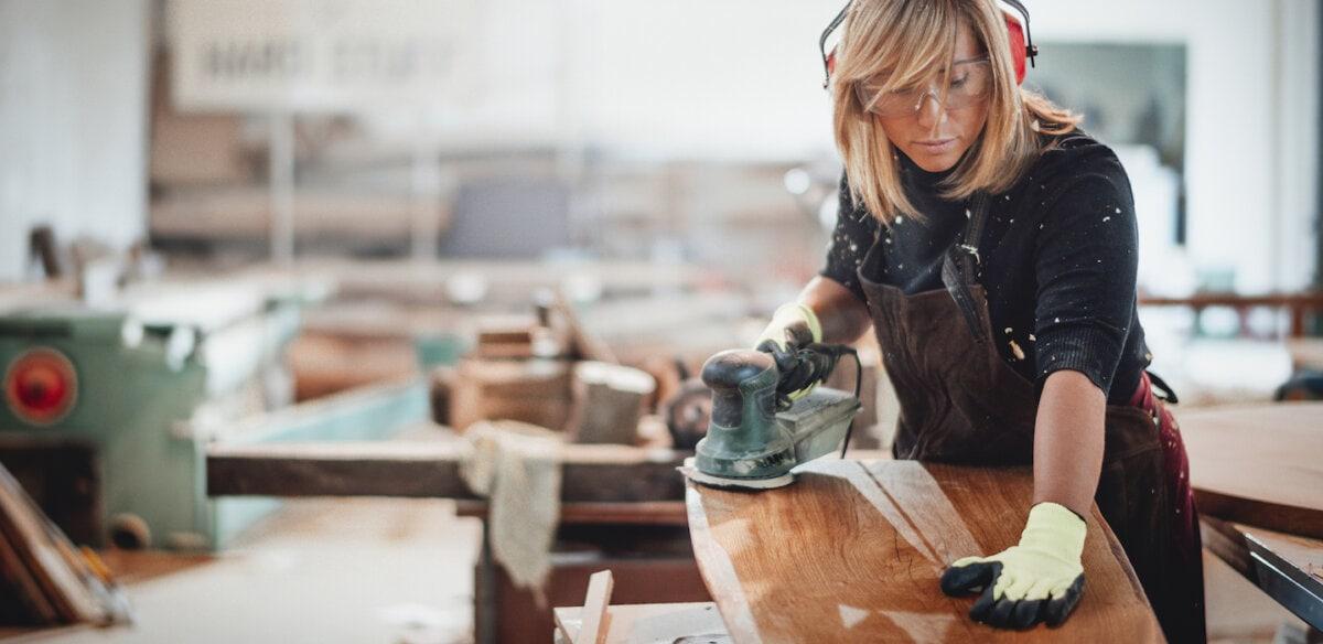 Carpenter polishing wooden panel