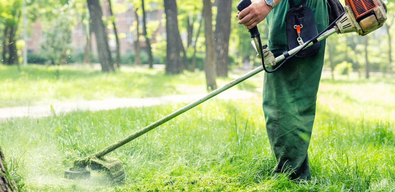 landscaper mowing tall grass