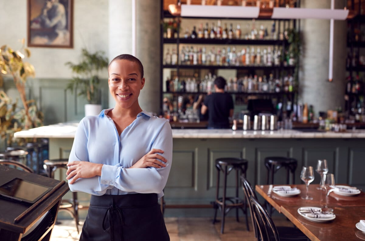 Confident Female Owner Of Restaurant Bar Standing By Counter
