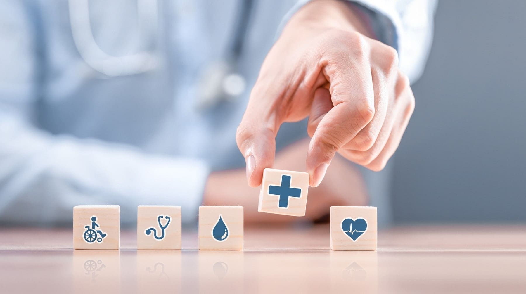 Hand arranging wood block with healthcare medical icon